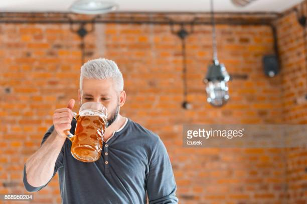 bearded man drinking beer in the pub - izusek stock pictures, royalty-free photos & images