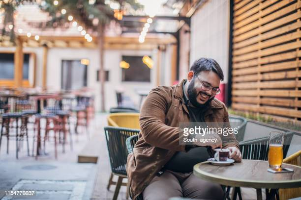 bearded man drinking coffee in a cafe garden - chubby stock pictures, royalty-free photos & images