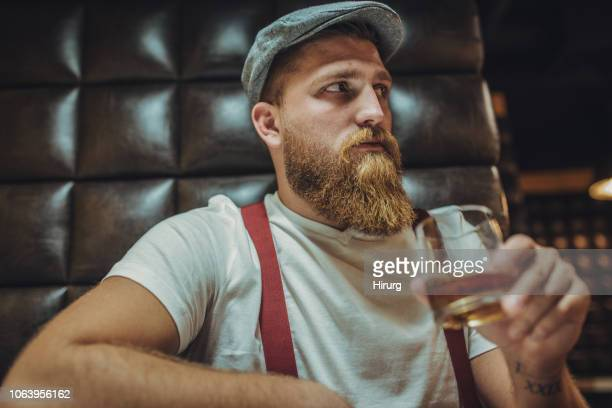 bearded man drinking whiskey - masculinity stock pictures, royalty-free photos & images