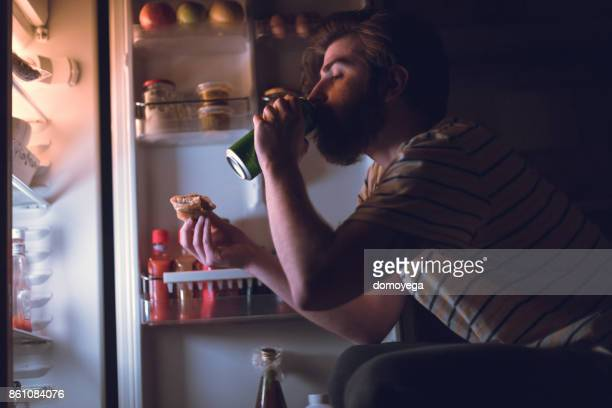 bearded man eating and drinking beer during the night - bulimia stock photos and pictures