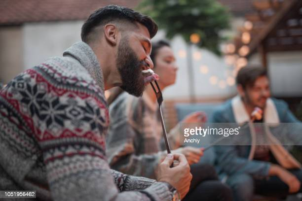 Bearded man eating marshmallows by the fire