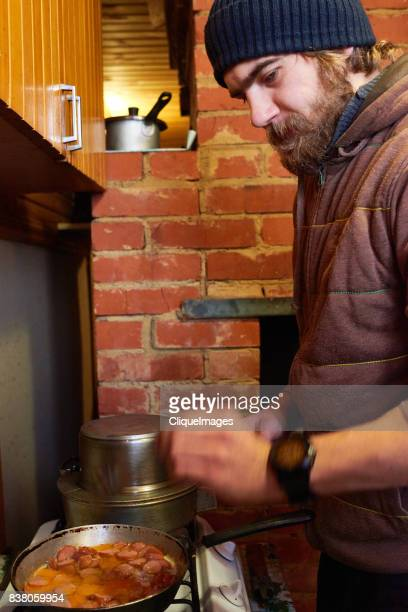 bearded man frying sausages - cliqueimages fotografías e imágenes de stock