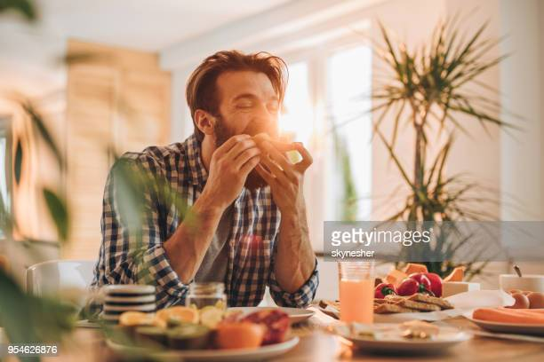 bearded man having a sandwich for breakfast at home. - biting stock pictures, royalty-free photos & images