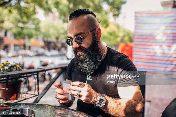 bearded man holding cigarette pack - cigarette packet stock pictures, royalty-free photos & images