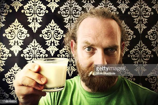 Bearded man holding milk