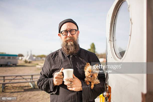Bearded man holding small dog and coffee cup