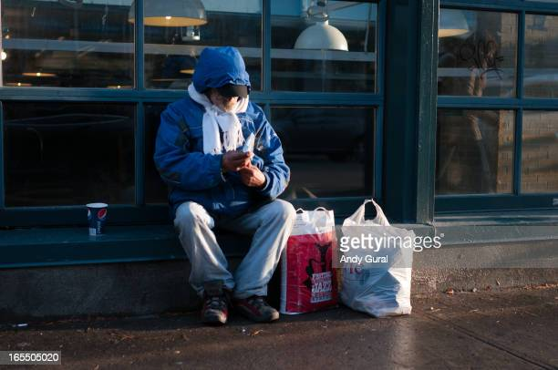 Bearded man in a blue hooded coat and white scarf sits on a store ledge to unwrap a cigarette. His shopping bags are next to him on the pavement. The...
