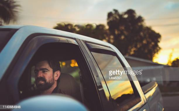 bearded man in a truck going for a drive at dusk - pick up truck stock pictures, royalty-free photos & images