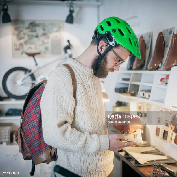bearded man in bicycle shop looking at bike seat