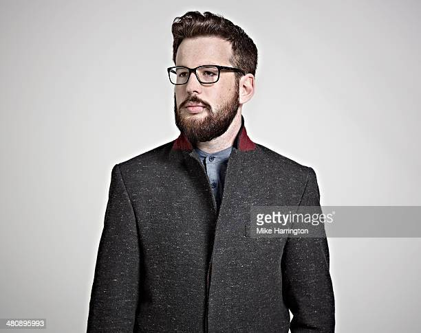 bearded man in coat and glasses looking sideways. - overcoat stock pictures, royalty-free photos & images