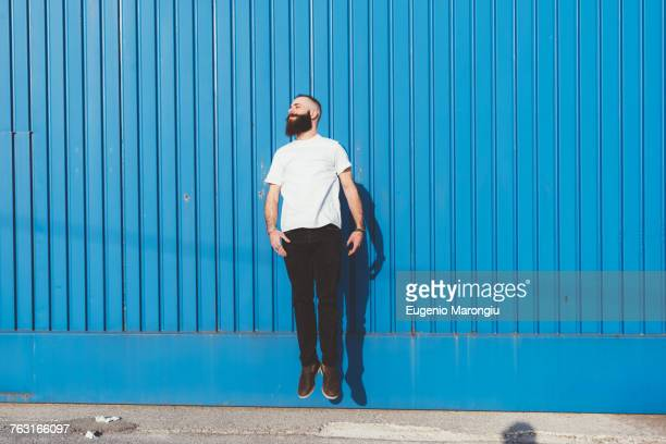 bearded man in front of blue wall jumping in mid air - hovering stock pictures, royalty-free photos & images