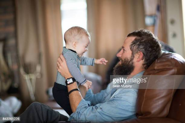 Bearded Man in Recliner Holding Laughing Baby