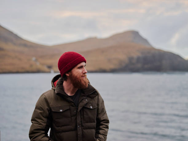 Bearded man in red beanie and jacket standing near ocean