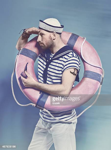 Bearded man in sailor style outfit holding lifebuoy