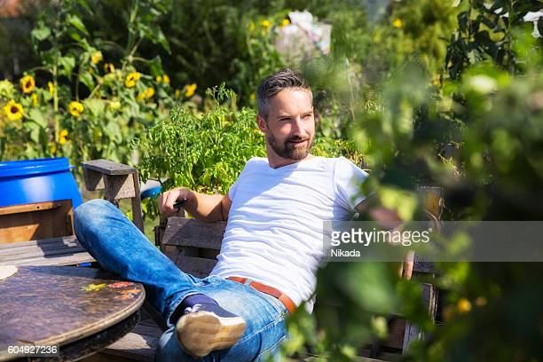 bearded man in urban garden - mid adult men stock pictures, royalty-free photos & images