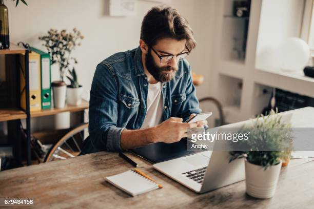 bearded man is using his phone - editor stock pictures, royalty-free photos & images