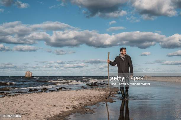 bearded man is walking along the beach. - schleswig holstein stock-fotos und bilder
