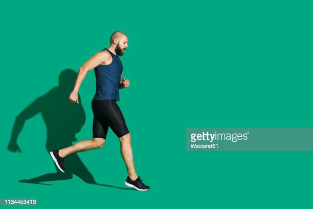 bearded man jogging in front of green background - green shorts stock photos and pictures