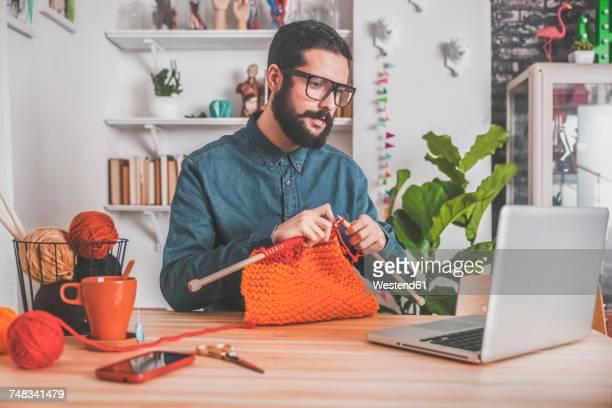 bearded man knitting at home using laptop for watching online tutorial - stricken stock-fotos und bilder