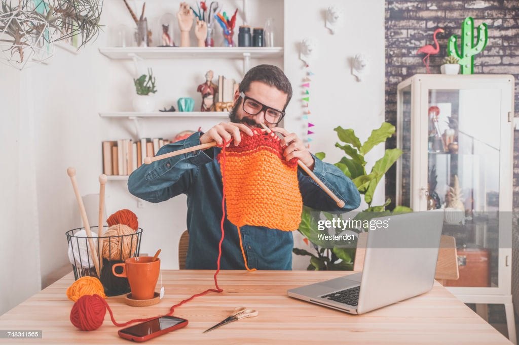 Bearded man knitting at home using laptop for watching online tutorial : Stock-Foto