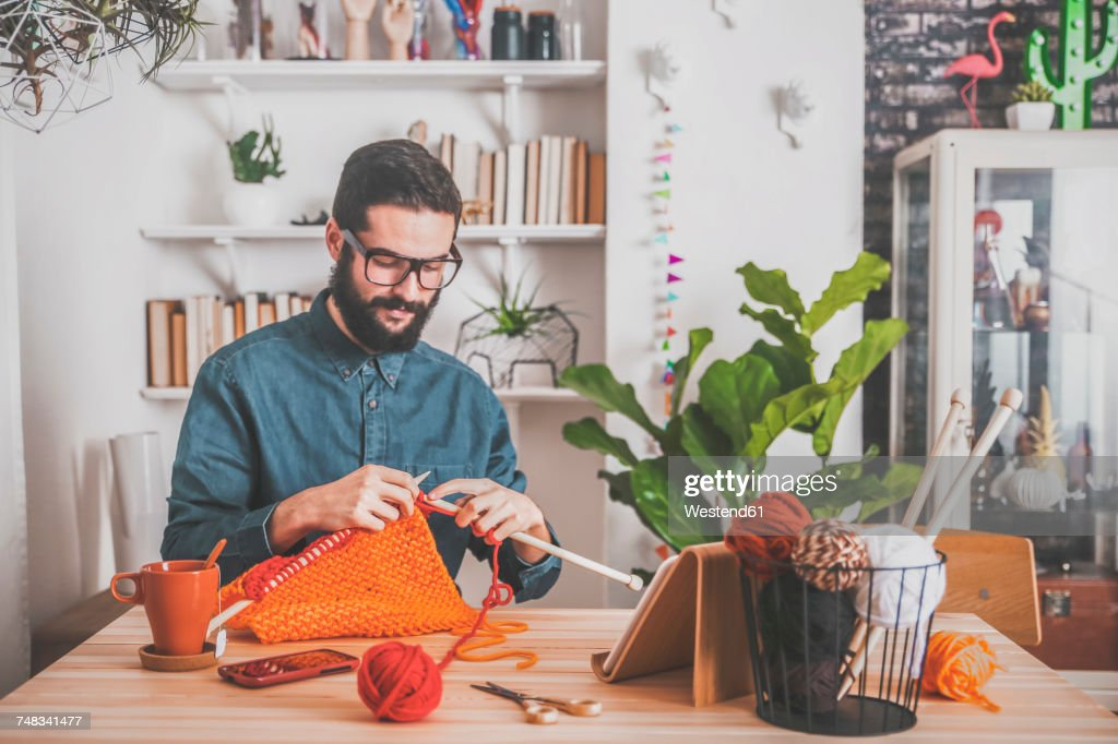Bearded man knitting at home using tablet for watching online tutorial : Stock-Foto