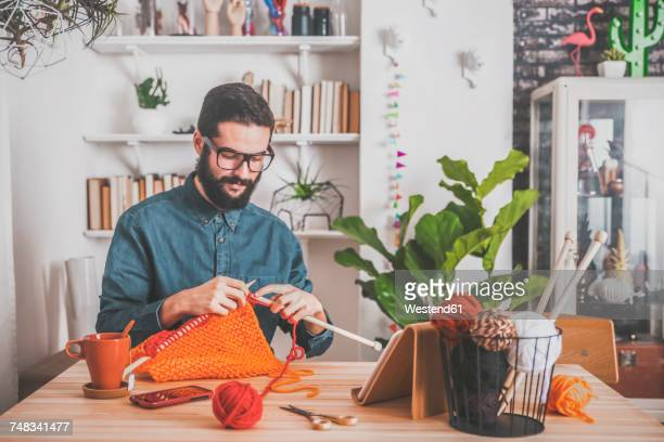 Bearded man knitting at home using tablet for watching online tutorial