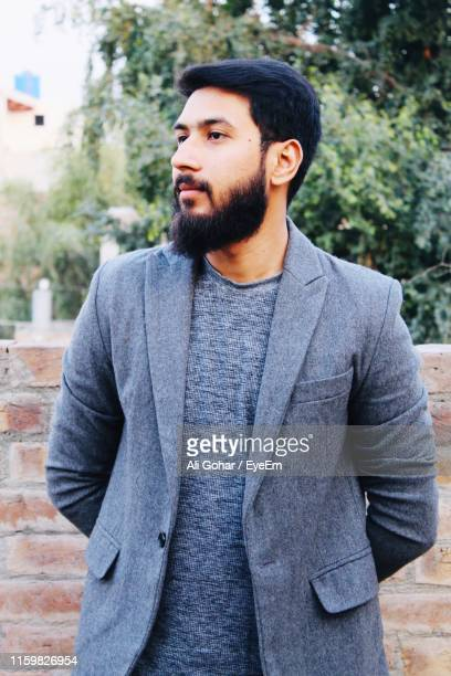 bearded man looking away against trees - pakistan stock pictures, royalty-free photos & images