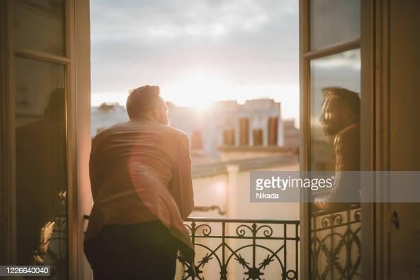 homme barbu regardant au-dessus de la ville au lever du soleil - regarder par la fenêtre photos et images de collection