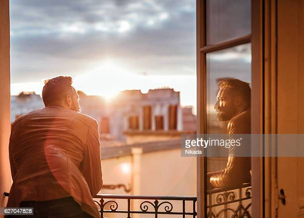 bearded man looking out over the city at sunrise - fenêtre photos et images de collection