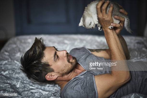 bearded man lying on bed at home holding kitten - linda oliver fotografías e imágenes de stock