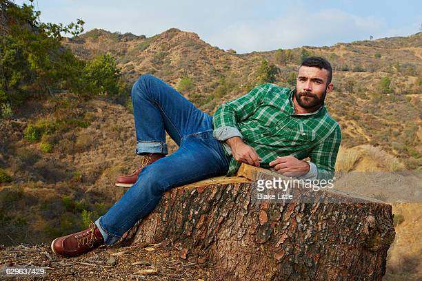 bearded man lying on stump - masculinity stock pictures, royalty-free photos & images