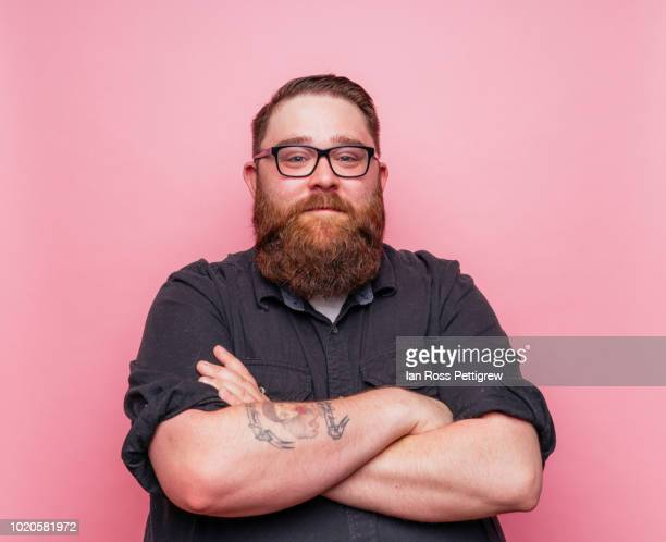 bearded man on pink background. - fat man beard stock photos and pictures