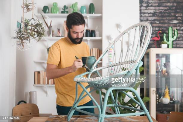bearded man painting wicker armchair at home - diy stock pictures, royalty-free photos & images