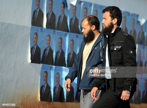 Bearded man pass in front of electoral posters of independent candidate to Algeria's presidential election Ali Benflis on the last day of the...