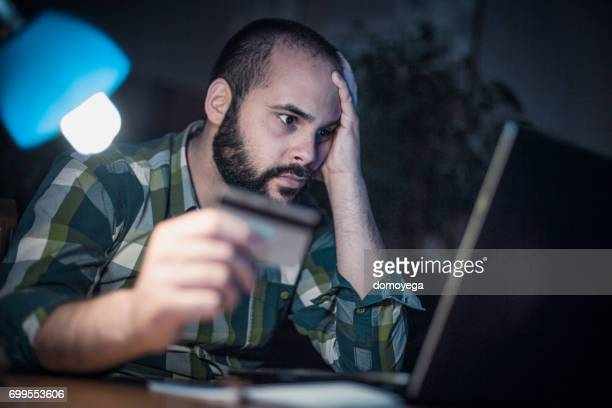 Bearded man paying with credit card from home at night