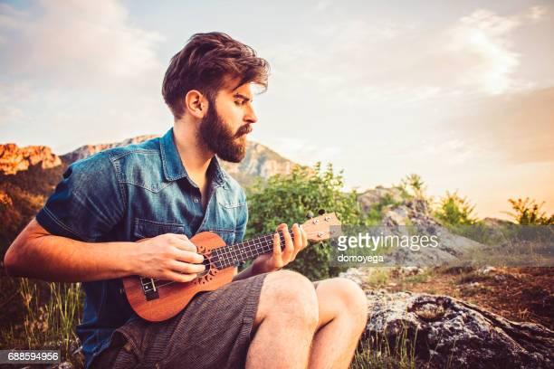 bearded man playing ukulele on top of hill - ukulele stock pictures, royalty-free photos & images