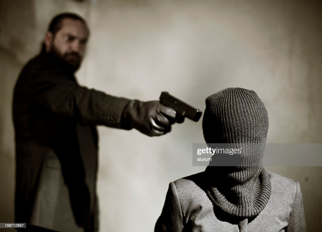 Bearded man pointing a gun at a man's temple to execute him : Stock Photo