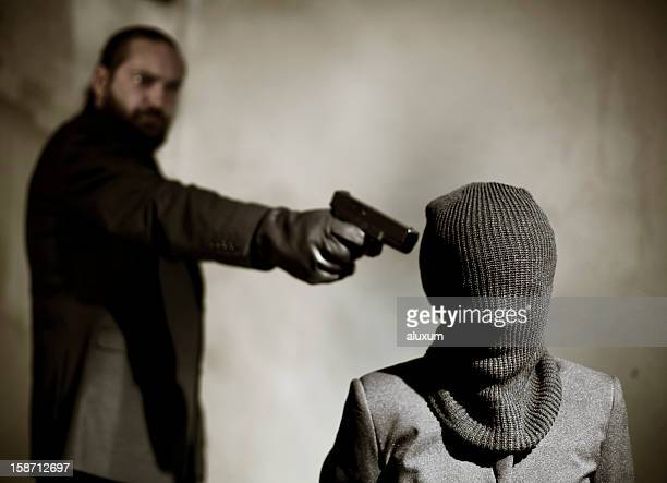 bearded man pointing a gun at a man's temple to execute him - execution stock pictures, royalty-free photos & images