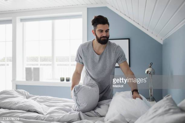 Bearded man preparing bed at home