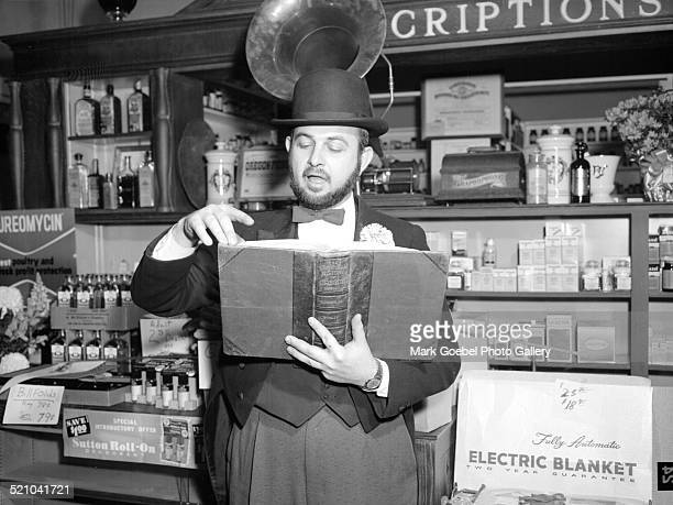 Bearded man reading in drugstore late 1950s