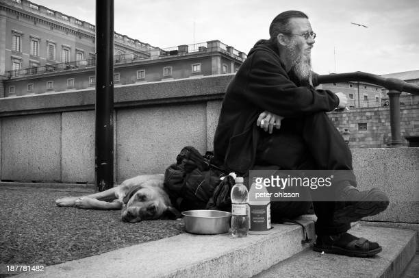 CONTENT] Bearded man resting on the street with his dog