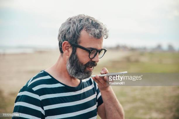 Bearded man sending voice message with smartphone on the beach