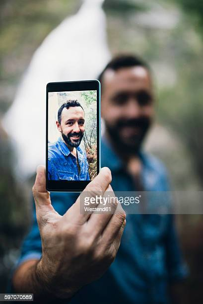 Bearded man showing selfie on display of his smartphone