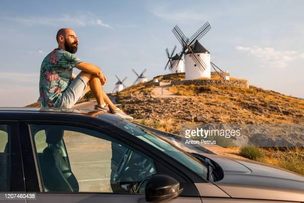 bearded man sits on the roof of the car on the background of windmills in consuegra, mancha, spain - castilla la mancha fotografías e imágenes de stock
