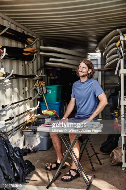 bearded man sitting inside open container filled with kayaking equipment, portland, maine, usa - portland maine stock pictures, royalty-free photos & images