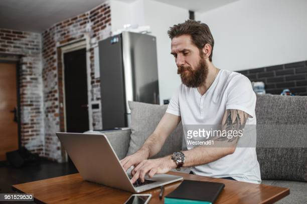 Bearded man sitting on the couch at home using laptop