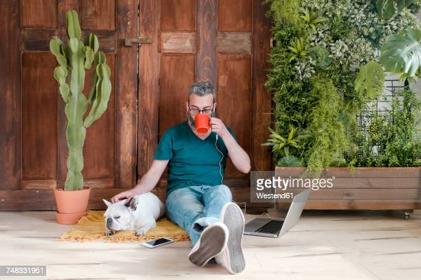 bearded man sitting with his dog on the floor at home drinking coffee - alleen één mid volwassen man stockfoto's en -beelden