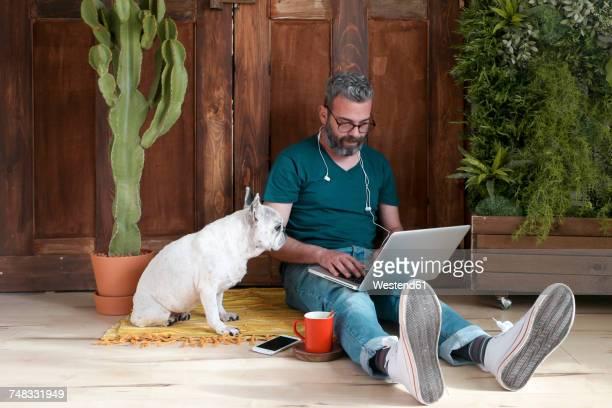 bearded man sitting with his dog on the floor at home using laptop - alleen één mid volwassen man stockfoto's en -beelden