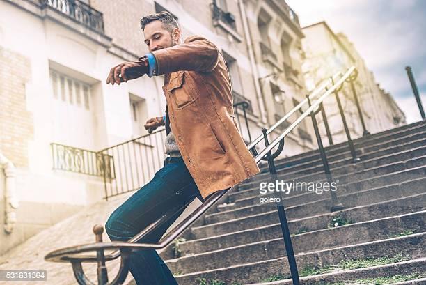 Homme barbu glisser le long de la balustrade Montmartre escaliers de fer