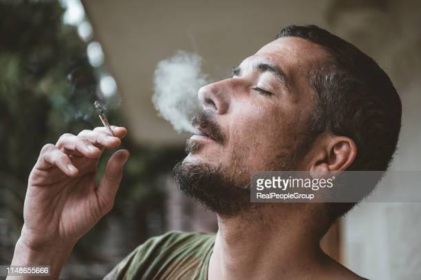 homme barbu fumant un joint de marijuana - hashish photos et images de collection